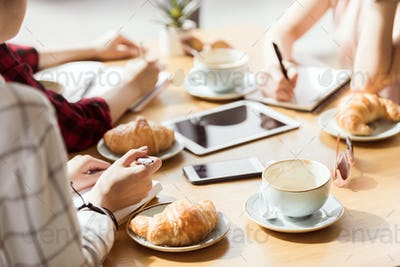 partial view of group of friends study together in cafe