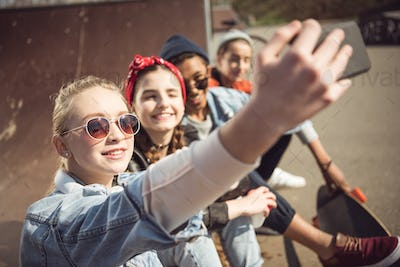 Smiling teenagers group taking hipster selfie while sitting together at skateboard park