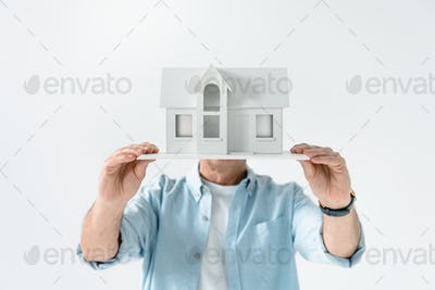 obscure view of man showing house model  isolated on white