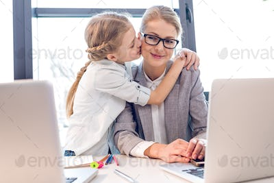 young mother and adorable daughter hugging and kissing in office with laptops