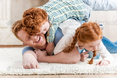 Happy father with adorable redhead children playing and having fun together on floor, family fun at