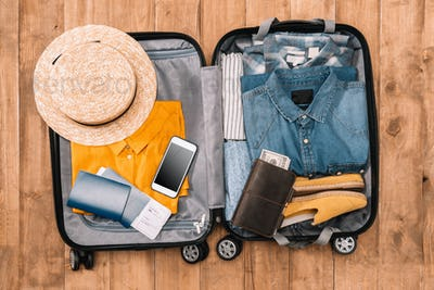 Ready for travel concept. Top view of essentials for tourist with clothes, accessories and gadgets,
