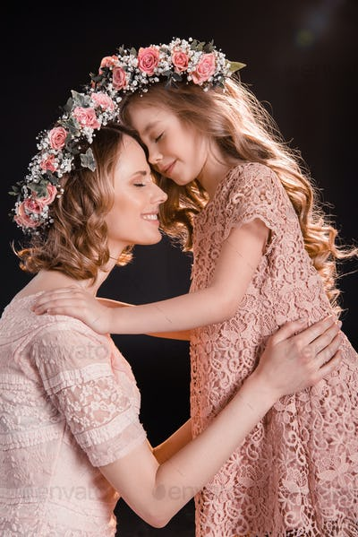 Happy mother and daughter in floral wreaths hugging and touching foreheads isolated on black
