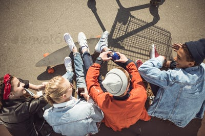 Overhead view of teenagers group sitting together and talking at skatepark