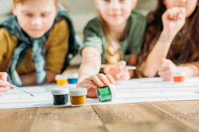 cute kids painting on paper with while lying on floor at home