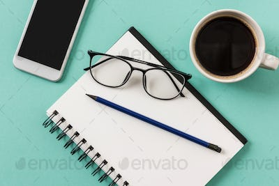 top view of notebook with cup of coffee and smartphone with glasses mock-up, small office home