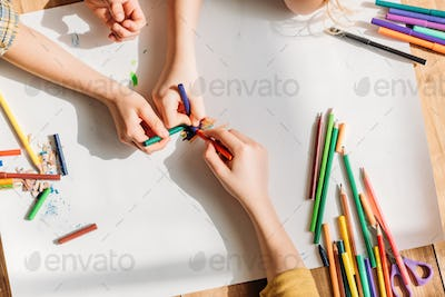 cropped view of cute kids drawing on paper with pencils while lying on floor