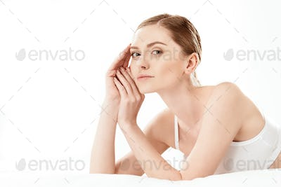 Beautiful young woman in white underwear lying isolated on white, skin care concept