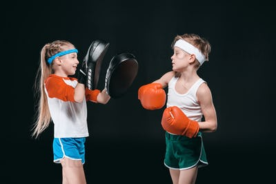 Side view of boy and girl in sportswear boxing isolated on black, activities for children concept
