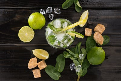 Top view of mojito cocktail in glass and fresh ingredients on dark wooden table top, cocktail drinks