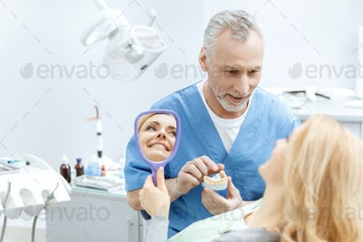 dentist showing jaws model to patient in dental clinic