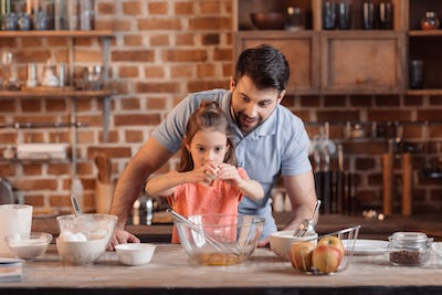 portrait of father and daughter making cookies in kitchen