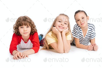 Cheerful kids lying on floor and have fun isolated on white