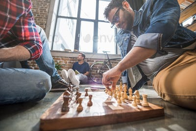 young men sitting on floor and playing chess on chess board
