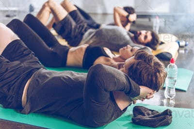 Sporty young people doing abs on yoga mats while exercising at the gym