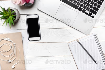 Top view of laptop, smartphone with blank screen and office supplies at workplace