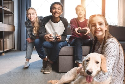 happy multicultural teenagers playing video games with joysticks at home, teenagers having fun