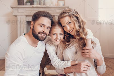 Happy young family with one child hugging and smiling at camera