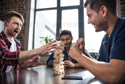 diverse group of young people playing jenga game