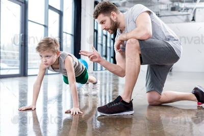 Boy doing push ups with coach at fitness center
