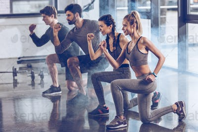 group of athletic young people in sportswear doing lunge exercise at the gym, aerobic fitness