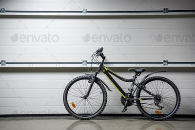 Mountain bike standing indoors at grey wall