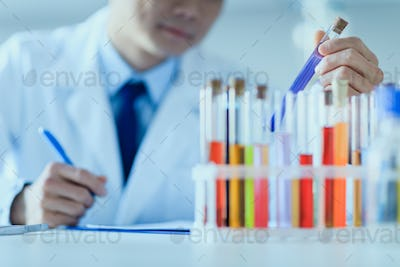 Cropped shot of scientist in lab coat holding test tube and taking notes, laboratory researcher
