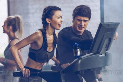 athletic young sportswoman running on treadmill at the gym, fitness couple gym concept