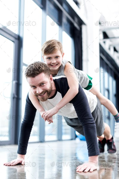Man doing push ups with boy on his back