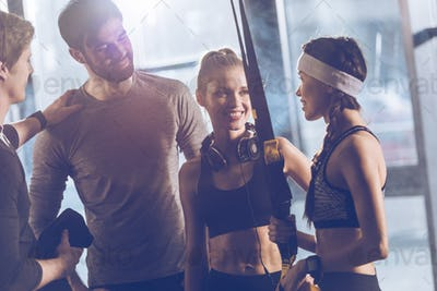 portrait of group of sportive people near trx equipment in gym