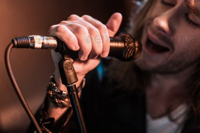 Cropped shot of young male singer with microphone on stage