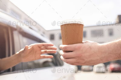 partial view of woman sitting in car and buying coffee to go