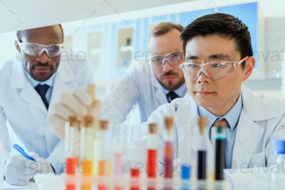 Multiethnic group of scientists in protective eyeglasses working together in chemical laboratory
