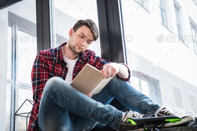 concentrated man reading book while sitting on window sill