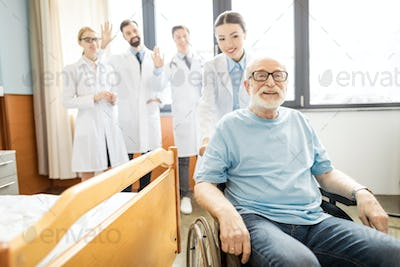 Group of young professional doctors looking at smiling senior patient in wheelchair, elderly man