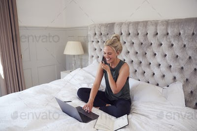 Businesswoman Sitting On Bed With Laptop And Mobile Phone Working From Home During Pandemic Lockdown