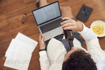 Businessman At End Of Day With Beer Wearing Loungewear And Shirt And Tie On Laptop Working From Home
