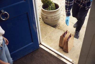 Close Up Of Food Delivery Driver Putting Takeaway On Doorstep Outside House