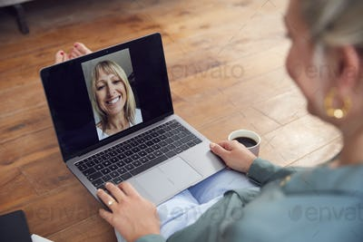 Woman With Laptop Having Video Chat With Friend Sitting On Floor At Home Relaxing