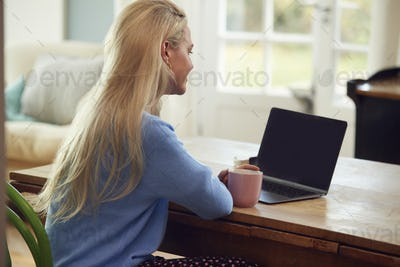 Rear View Of Woman Sitting At Table With Laptop Having Video Chat With Friend At Home