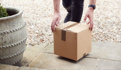 Close Up Of Delivery Driver Putting Package On Doorstep Outside House