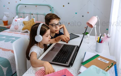 Boy helping his sister studying with computer