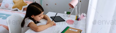 Girl studying at home with mask on table