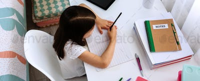 Girl studying at home with tablet and mask on table
