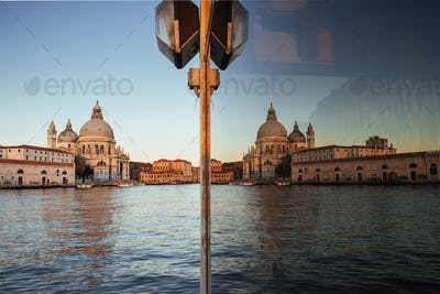 View and reflection in the glass of the old cathedral of Santa Maria della Salute at sunset