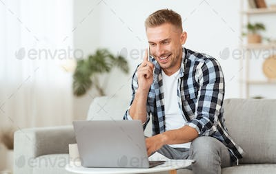 Portrait of successful smiling man using pc talking on cellphone
