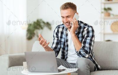 Portrait of successful man talking on smartphone using pc