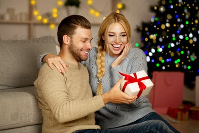 Emotional woman looking at Christmas gift in her man hands