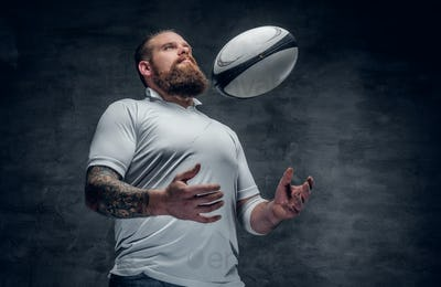 Portrait of bearded rugby player with tattoos on his arms
