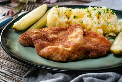 Pork chop served with mashed potatoes and pickled cucumber.